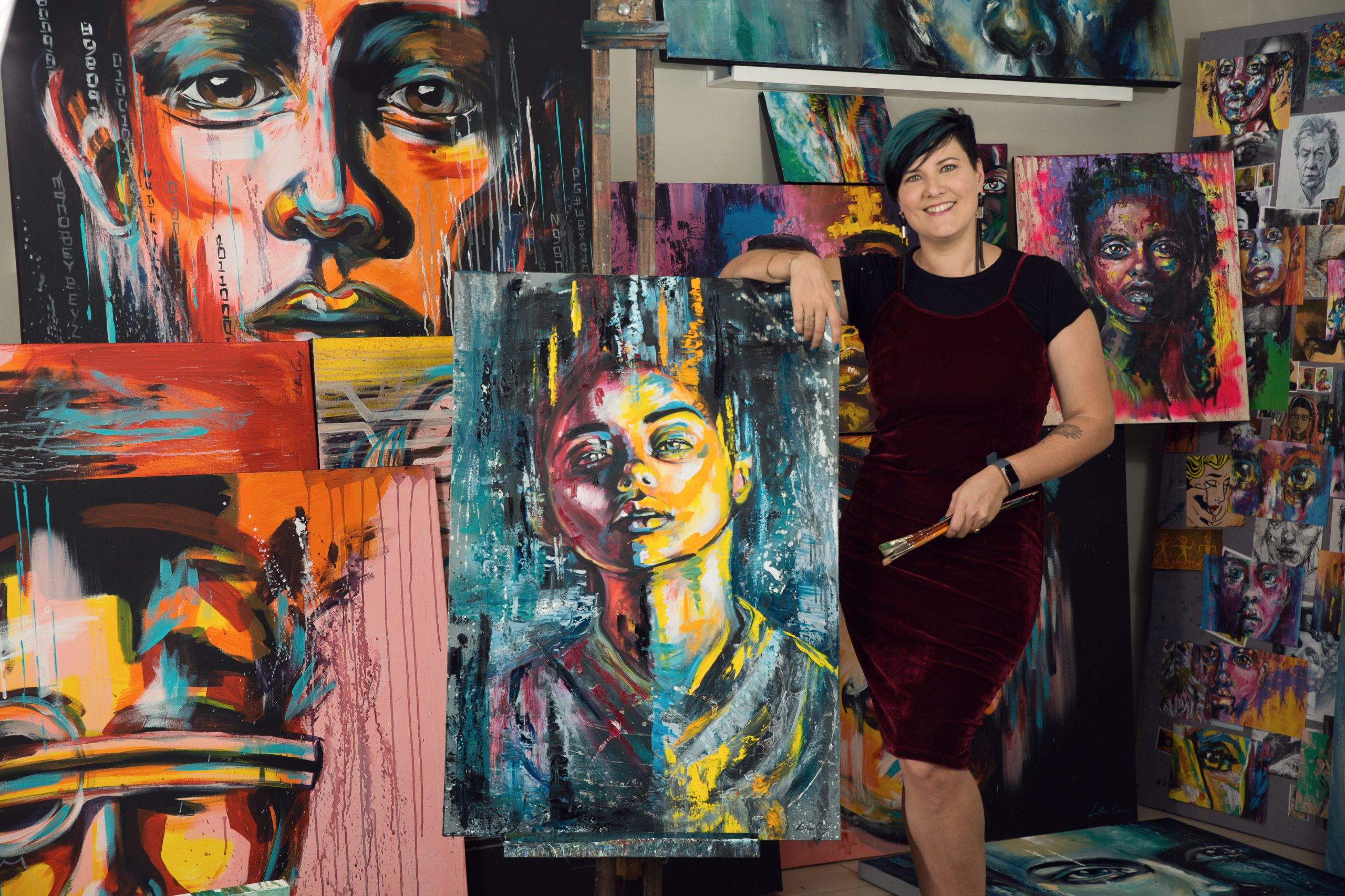Artist Lillian Gray standing next to her easel with a paint brush