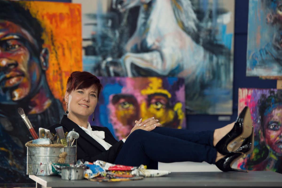 Artist Lillian Gray wearing a business suite and heel at her art studio desk.